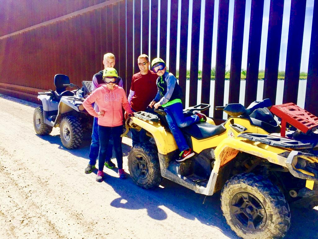Family Riding ATV's Near The Border Fence
